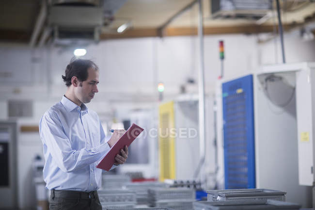 Male engineer inspecting equipment at industrial plant — Stock Photo