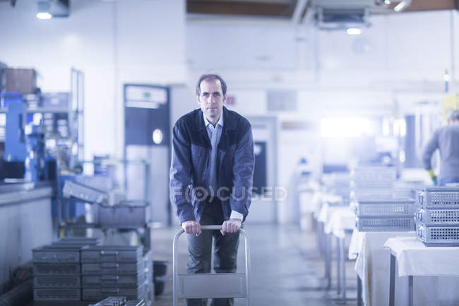 Male engineer pushing cart at industrial plant — Stock Photo