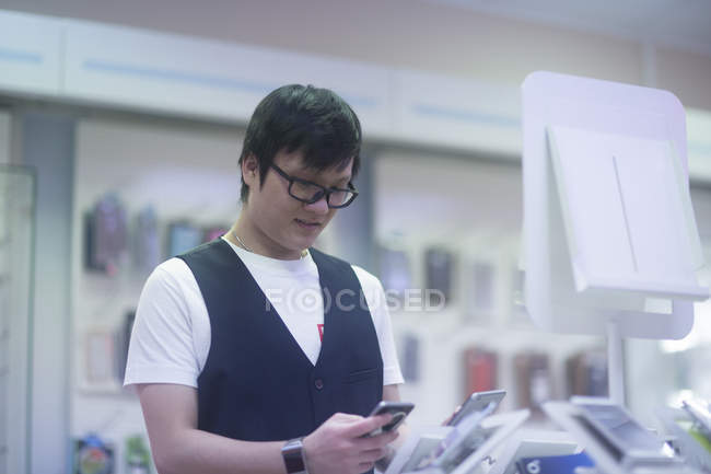 Asian man choosing smartphone at electronics store — Stock Photo