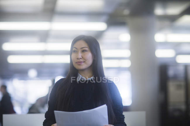 Woman holding documents in office and looking away — Stock Photo