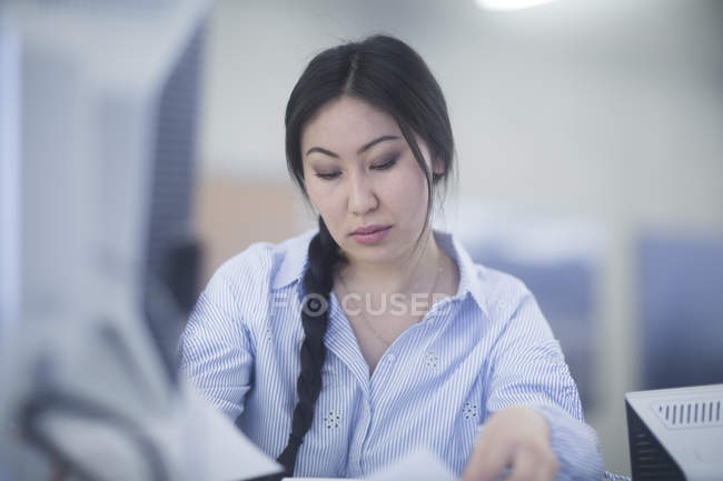 Woman sitting at office desk and looking down — Stock Photo