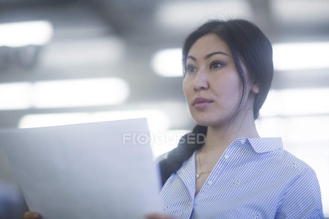 Pensive woman holding papers and looking away — Stock Photo