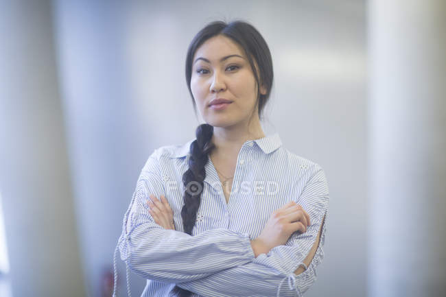 Asian woman standing with arms folded and looking in camera — Stock Photo