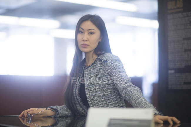 Woman sitting at table looking in camera — Stock Photo