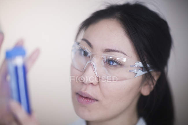 Female scientist in safety goggles looking at blue test tube — Stock Photo