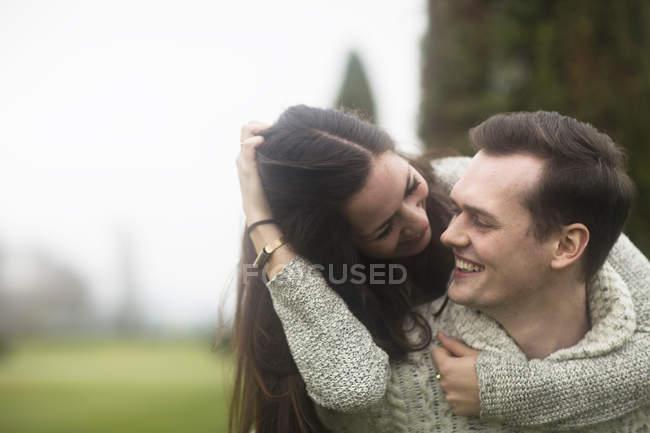 Lächelnde Frau Freund von hinten umarmt — Stockfoto