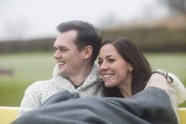 Young Couple Cuddling Under Blanket Outdoors Stock Photo
