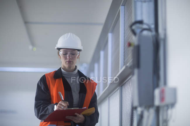 Female engineer in protective clothing writing in clipboard indoors — Stock Photo