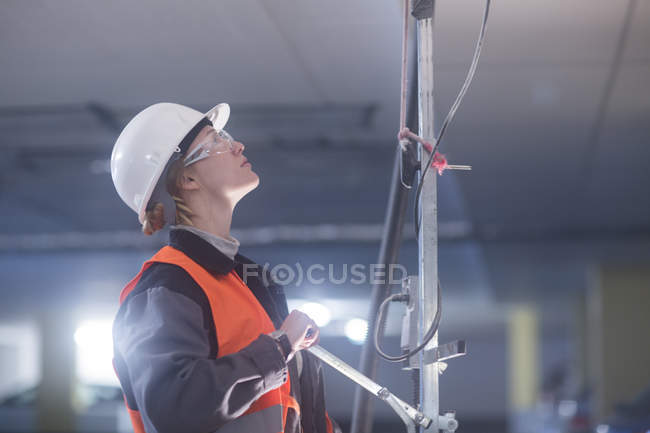 Female engineer in protective clothing adjusting equipment — Stock Photo
