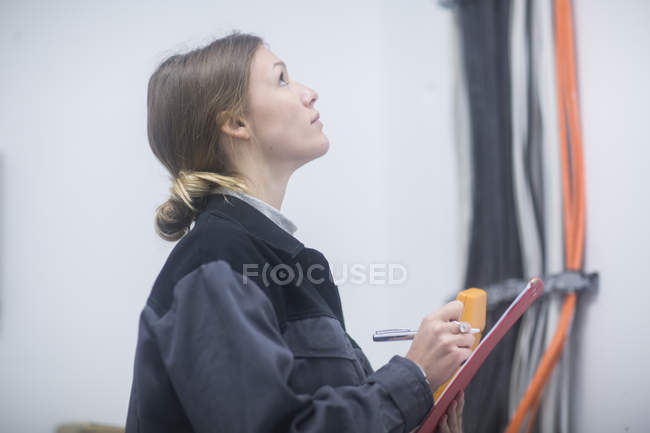 Female factory worker writing down test readings in clipboard — Stock Photo
