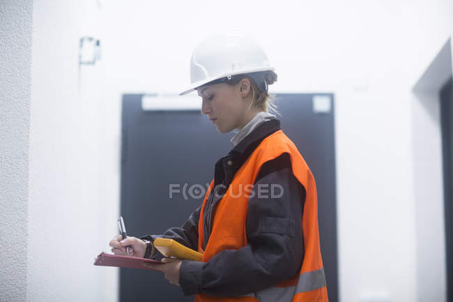 Female engineer in hard hat writing down equipment readings in clipboard — Stock Photo