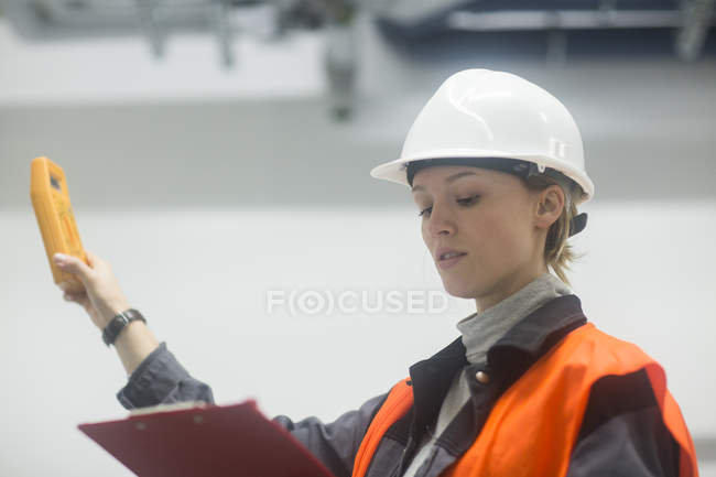 Female engineer in hard hat examining room with test equipment — Stock Photo