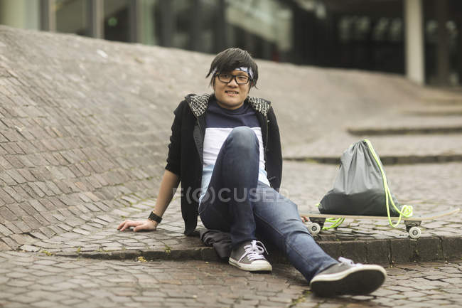 Young man sitting on cobblestoned street with skateboard and sport bag — Stock Photo