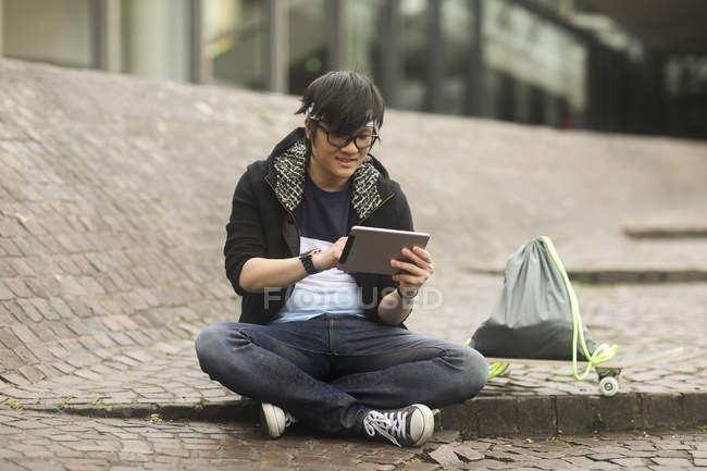 Молодой человек с оголовьем, используя цифровой планшет на улице — стоковое фото
