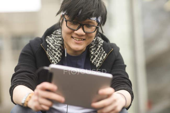 Азиатские человек с наушники с использованием цифрового планшета — стоковое фото