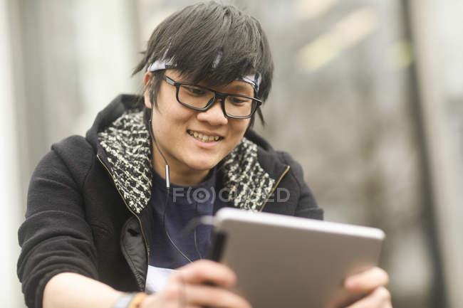 Asiatischer Mann mit Ohrhörer mit digital-Tablette — Stockfoto