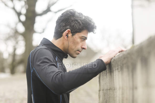 Male athlete with earbuds leaning on wall in street — Stock Photo