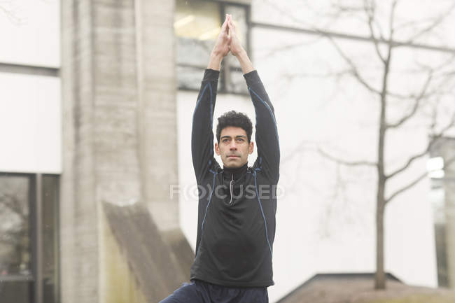 Man practicing yoga tree pose at street — Stock Photo