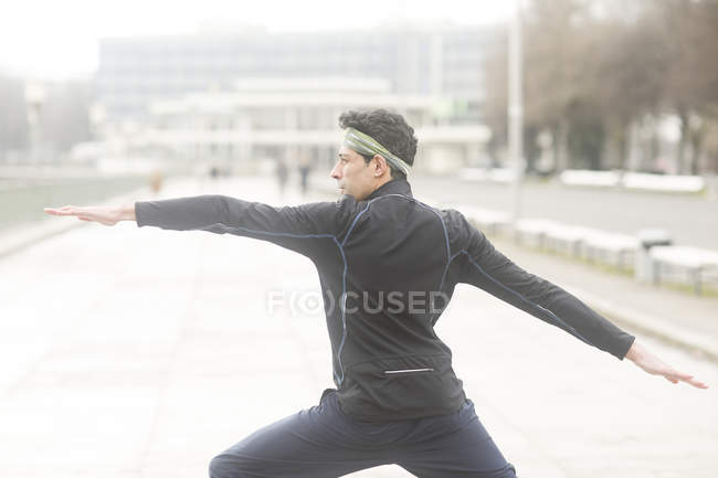 Man practicing yoga warrior pose at street — Stock Photo