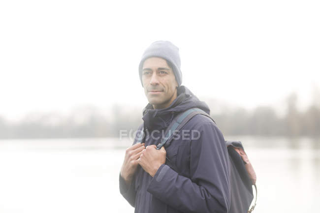Male tourist with backpack looking away outdoors — Stock Photo