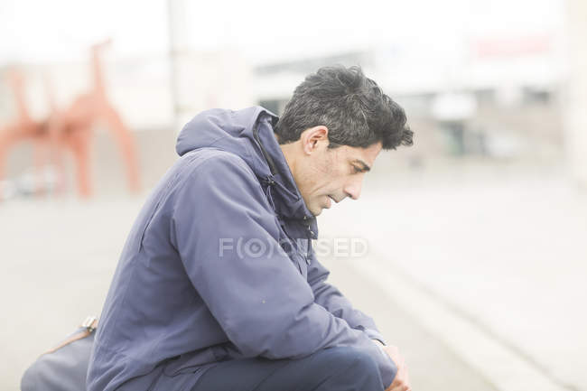 Mid adult man in jacket sitting on sidewalk — Stock Photo