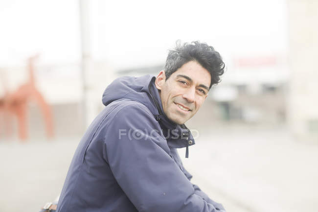 Mid adult man in jacket sitting on street and looking in camera — Stock Photo