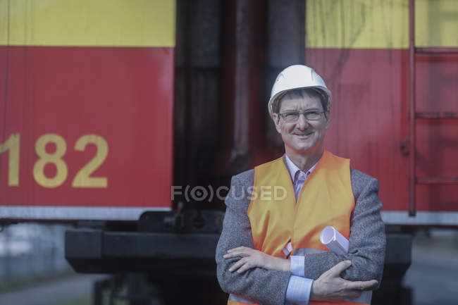 Construction engineer standing with blueprints in front of industrial truck — Stock Photo
