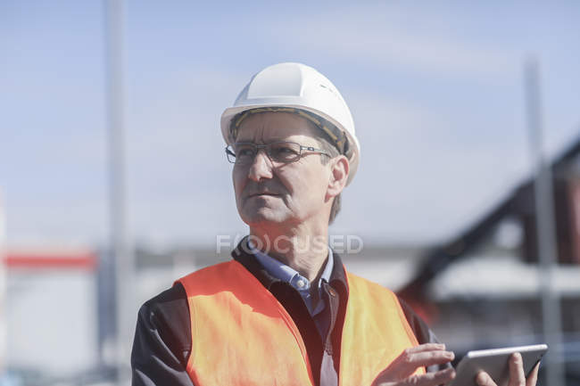 Industrial worker using digital tablet and looking away on construction site — Stock Photo