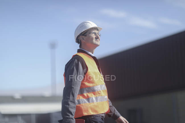 Construction worker walking at workplace and looking up — Stock Photo