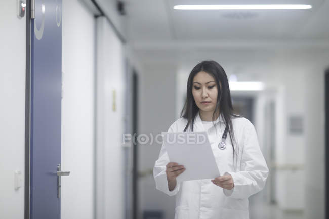 Female doctor walking in hallway with medical records — Stock Photo