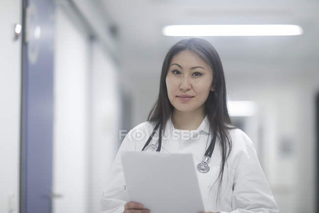 Female doctor standing in hallway with medical records — Stock Photo
