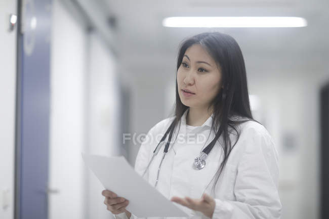 Female doctor with medical records talking in hospital — Stock Photo