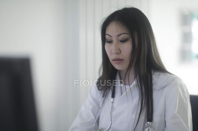 Female doctor working in clinic office — Stock Photo