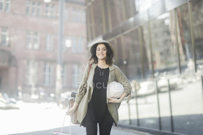 Young woman in trench coat walking with white hard hat in city — Stock Photo