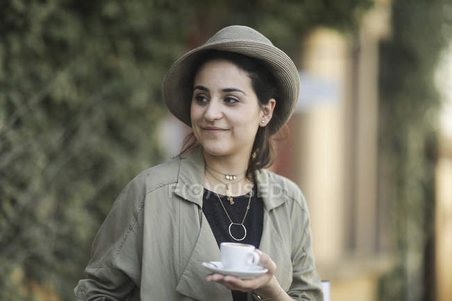 Young woman in stylish hat holding cup of coffee — Stock Photo