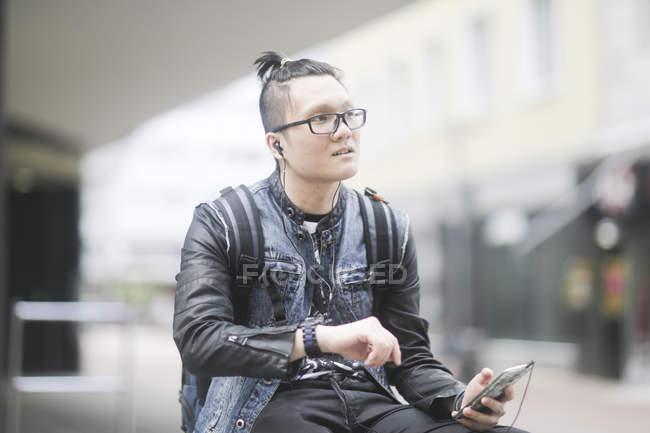 Людина з смартфон, перевіряючи час з наручні годинники в місті — стокове фото