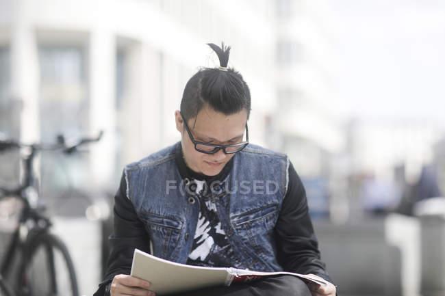 Молодых взрослых чтения журнала в городе — стоковое фото