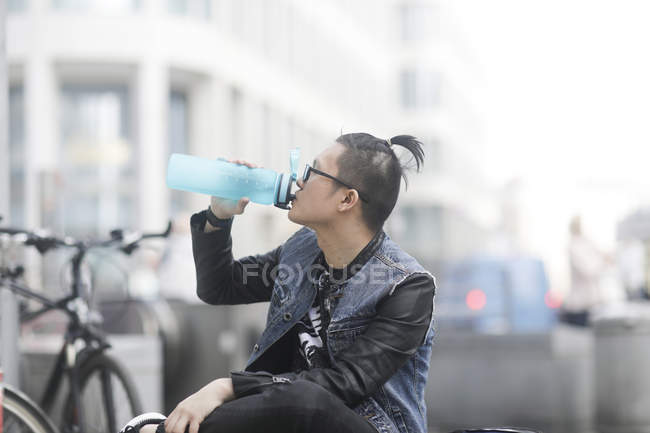 Young man drinking from sports water bottle — Stock Photo