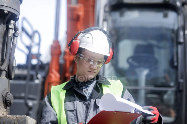 Male civil engineer reading documentation on construction site — Stock Photo