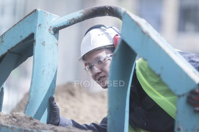 Construction worker examining heavy equipment on building site — Stock Photo
