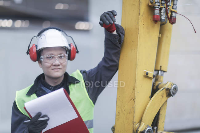 Male civil engineer with clipboard leaning on machinery on construction site — Stock Photo