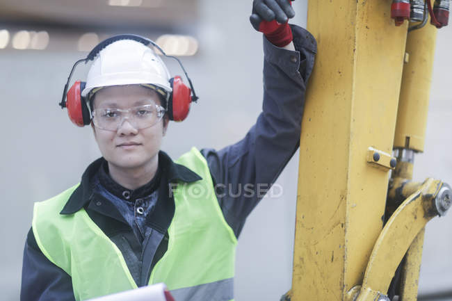 Construction worker leaning on machinery on building site — Stock Photo