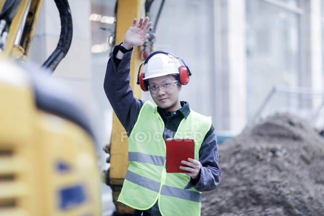 Construction worker with digital tablet making stop gesture on building site — Stock Photo