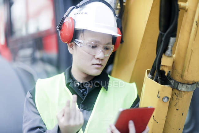 Construction worker with digital tablet making beckoning gesture on building site — Stock Photo