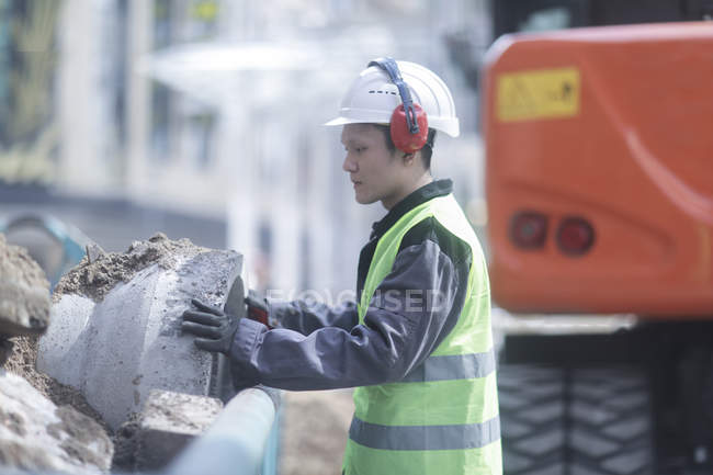 Construction worker working with concrete pipe on building site — Stock Photo