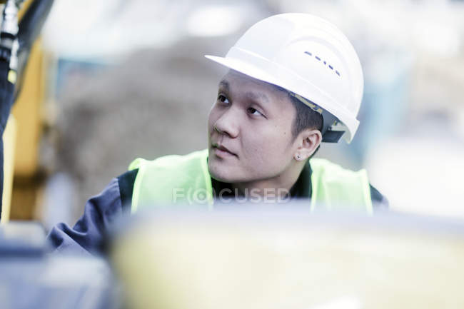 Male civil engineer in hard hat looking up on construction site — Stock Photo