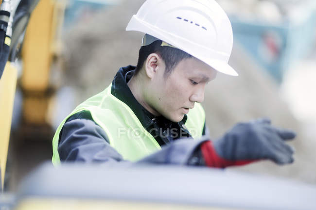 Male civil engineer in hard hat looking down on construction site — Stock Photo