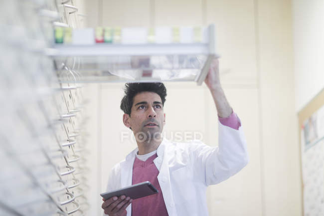 Mid adult pharmacist with digital tablet inspecting drugs in drawers — Stock Photo