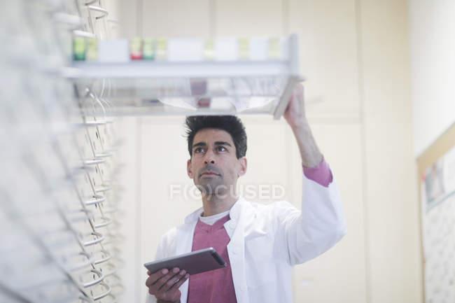 Metà adulto farmacista con tavoletta digitale ispezione farmaci nei cassetti — Foto stock