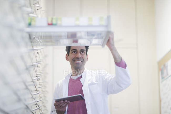 Cheerful pharmacist with digital tablet inspecting drugs in drawers — Stock Photo